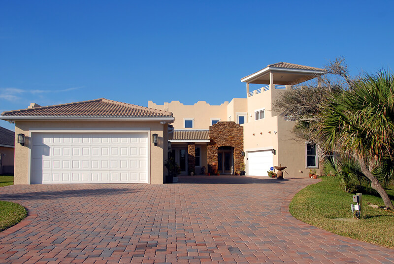 white and beige house with interlock driveway
